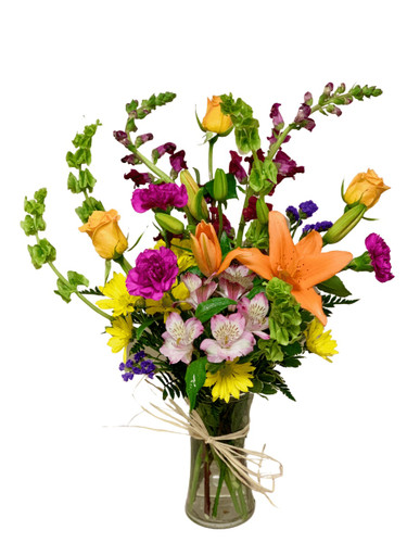 Bold Babe:  arrangement of lilies, roses, snapdragons, Bells of Ireland, and more, with seasonal greens, in a clear glass gathering vase with raffia trim