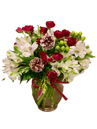 Berries in the Snow:  arrangement of white alstromeria, red spray roses, pinecones, hypericum, and winter greens in a clear glass ginger vase with a red bow