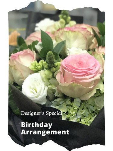 The Designer's Special Birthday Arrangement includes the florist's choice of fresh blooms in a vibrant color palette, accented with seasonal greens, and beautifully presented for the gift recipient.