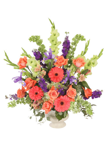 'Rest in Power'- sympathy arrangement of roses, gladiola, gerbera, hydrangea, and irises, with glossy greens, in a classic funeral urn.