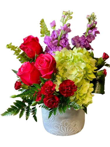 Modern Mood:  arrangement of hot pink roses, light pink stock, and green hydrangea, with sword fern and aspidistra leaves, in a boho-style stone container