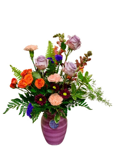 Delightful Dragonfly - arrangement of orange snapdragons, lavender roses, and peach carnations in a purple ceramic vase adorned with a keepsake dragonfly medallion