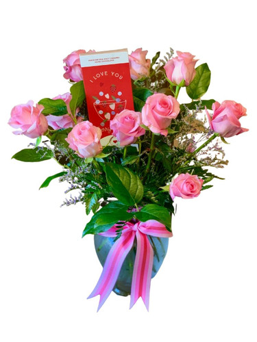 The Delectable Dozen - one dozen pink roses with a chocolate greeting card, presented in a clear glass Ming vase.