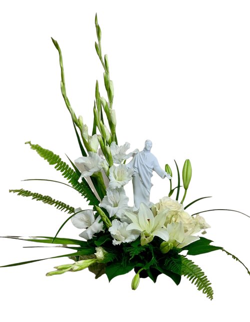 Perfect Light:  arrangement of white flowers including roses, lilies, and gladiola, and seasonal greens, with a keepsake figurine of porcelain bisque.