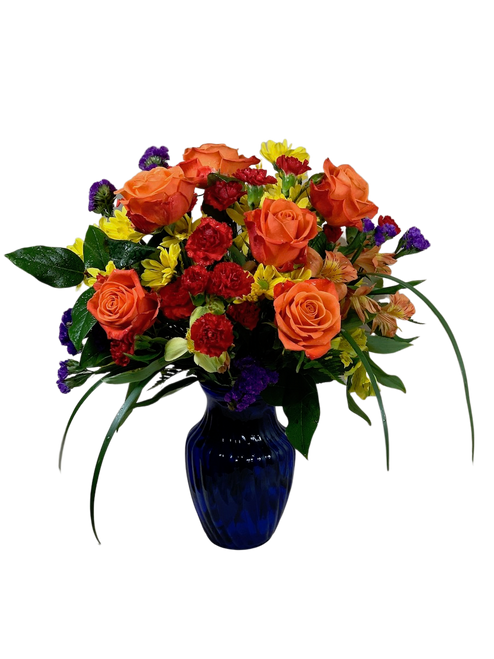 Life of the Party:  arrangement of orange roses, red carnations, yellow daisies, and alstromeria, in a cobalt blue glass vase