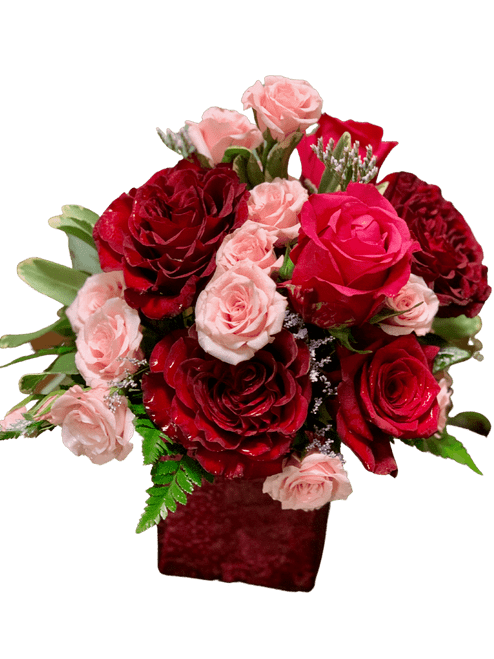 Sweet and Spicy:  arrangement of red and hot pink roses with soft pink spray roses, in a cube of red and pink shimmer glass