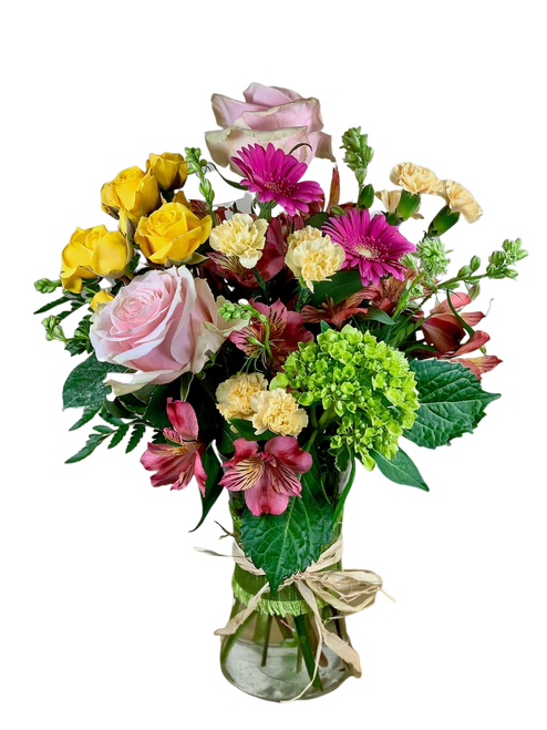 Blooms in Vogue:  arrangement of pink roses, yellow rose, pink gerbera, and green hydrangea, in a gathering vase trimmed with ribbon and raffia