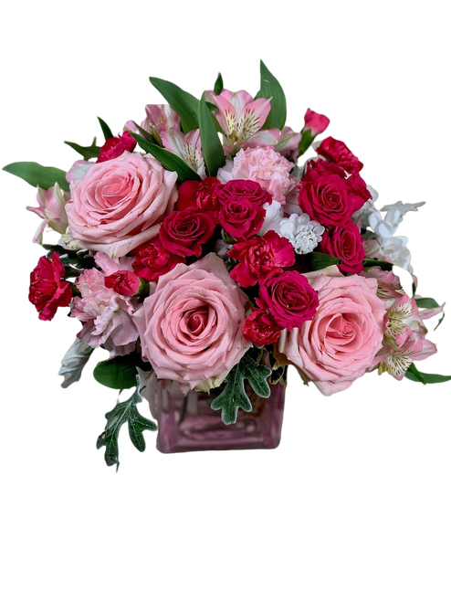 Pink About It:  Arrangement of  roses, spray roses, alstromeria, and carnations in shades of light pink and hot pink, in a pink glass cube.
