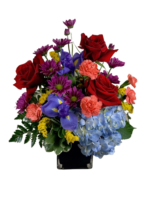 Bright Bunch:  arrangement of red roses, blue hydrangea, purple iris, and orange carnations, in a blue glass cube