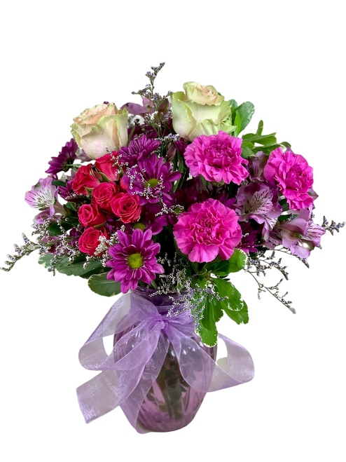 You Look Mauvelous:  arrangement of pink roses, lavender carnations,  hot pink spray roses, purple daisies, and purple alstromeria in a lavender glass vase, accented with sheer ribbon trim.