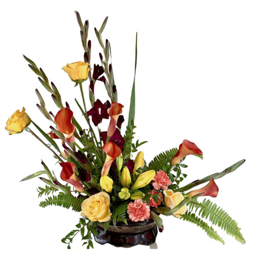Amber Fields:  Tribute arrangement of purple gladiola, yellow roses, orange callas, and yellow lilies, with swordfern and huckleberry, in a low oval container