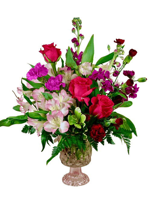 At First Blush:  romantic arrangement of hot pink roses, light pink alstromeria, fuschia stock, and burgundy min-carnations, in a compote dish of faceted pink glass