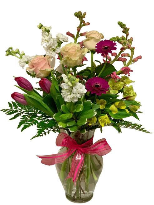 Lovely Day:  Arrangement of snapdragons, tulips, roses, gerbera, and more, in shades of pink, yellow, purple, and white, presented in a clear glass Ming vase