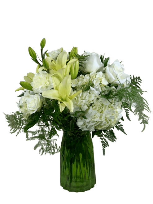 Whispered Wishes:  An arrangement of hydrangea, roses, spray roses, alstromeria, and carnations in shades of white and cream, in a tall vase of fluted green glass