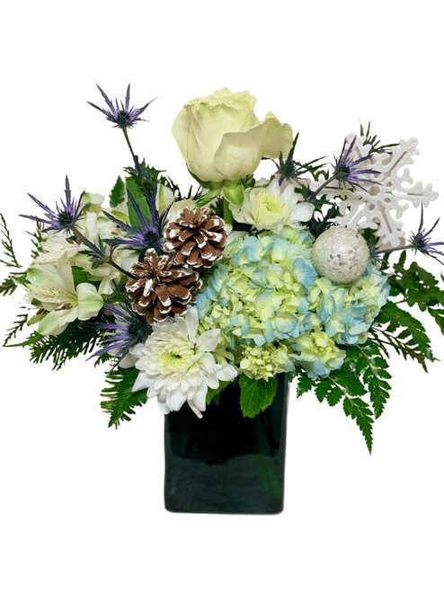 Star of Wonder:  Arrangement of blue hydrangea and thistle with white roses, alstromeria, and cushion poms, with winter accents, in a retangular vase of sapphire blue glass