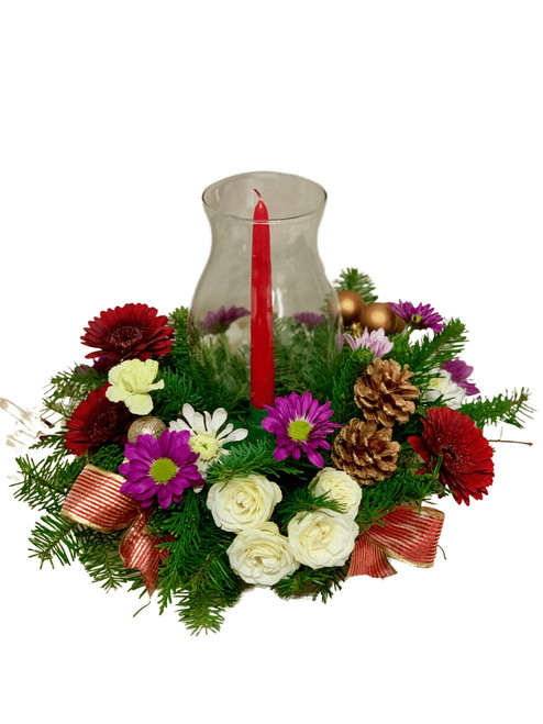 All Aglow Centerpiece - floral centerpiece of gerbera, spray roses, daisy poms, and miniature carnations, with winter greens, pinecones, holiday ornaments, and ribbons accents, topped with a bright red candle in a clear glass hurricane