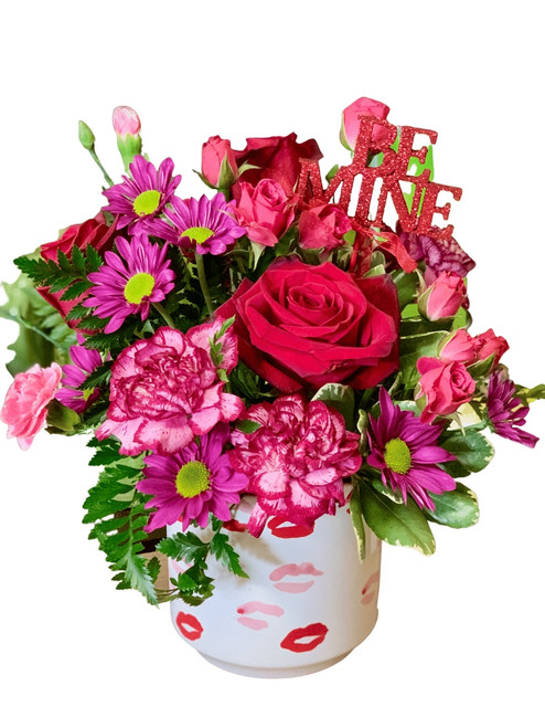 Dammi un Bacio - arrangement of roses, carnations and more, in shades of red , pink, and purple, presented in a white ceramic container decorated with kisses
