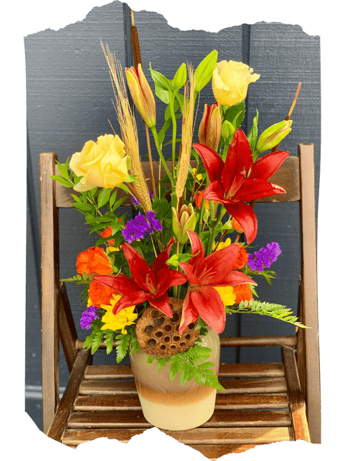 Autumn Glory:  seasonal arrangement of red lilies, yellow roses, orange spray roses, and purple statice, with wheat stalks and brown cattails, in a resuable ceramic crock.