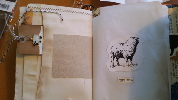 Back pages of book with large side pocket and tag inside with a sheep charm