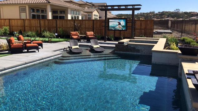 Outdoor TV cabinet by pool in backyard