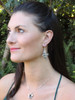 Model is wearing Mocking Jay Earrings & Orchid Charm
