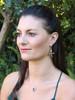 Model is wearing bronze Mocking Jay Earrings & Silver Orchid Charm