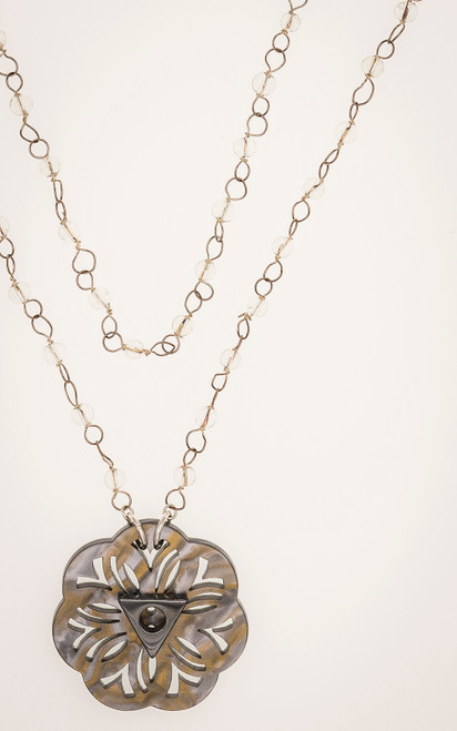 Mother of pearl carved flower pendant with a hematite center