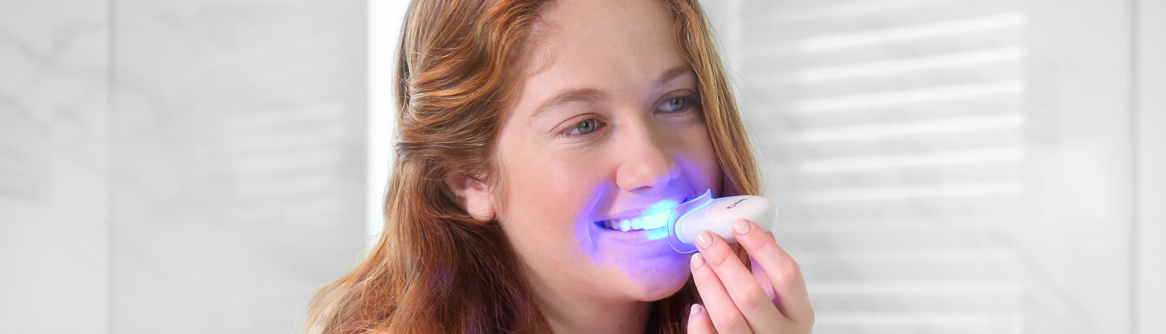 Red haired girl holding the Crest Blue Light in front of her mouth | Crest White Smile
