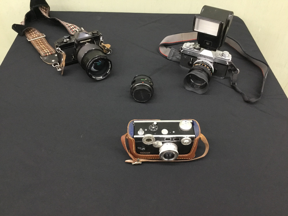 3 vintage cameras and 1 extra lens.
