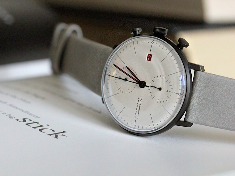 max bill Chronoscope 100 Jahre Bauhaus 100 years of Bauhaus - time to celebrate: The design features of the max bill Chronoscope 100 Jahre Bauhaus, limited to 1000 watches, are influenced by the architecture of the Bauhaus building. The white walls as well as the anthracite façade are reflected in the matt silver dial and the case of the watch. The grey strap is based on the Bauhaus building element: Concrete. Red accents accentuate the colour scheme of the well-known red entrance door of the Bauhaus. The back of the watch is a true journey through time: The observer can get a look at the self-winding movement through the historical, famous window front on the case back.  Ref. Nr. 027/4902.02