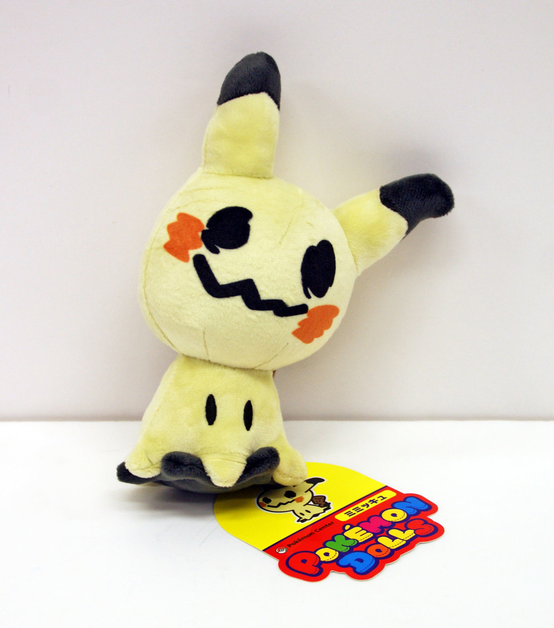 A Mimikyu plush leans against the wall.