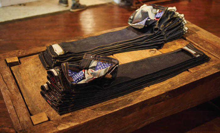 Raw denim jeans store display with American flag pocket bags