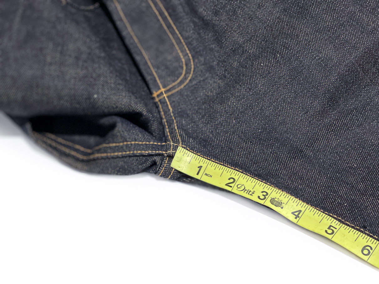 Photo shows how to measure inseam on jeans by starting at the center of the flat-felled seam.