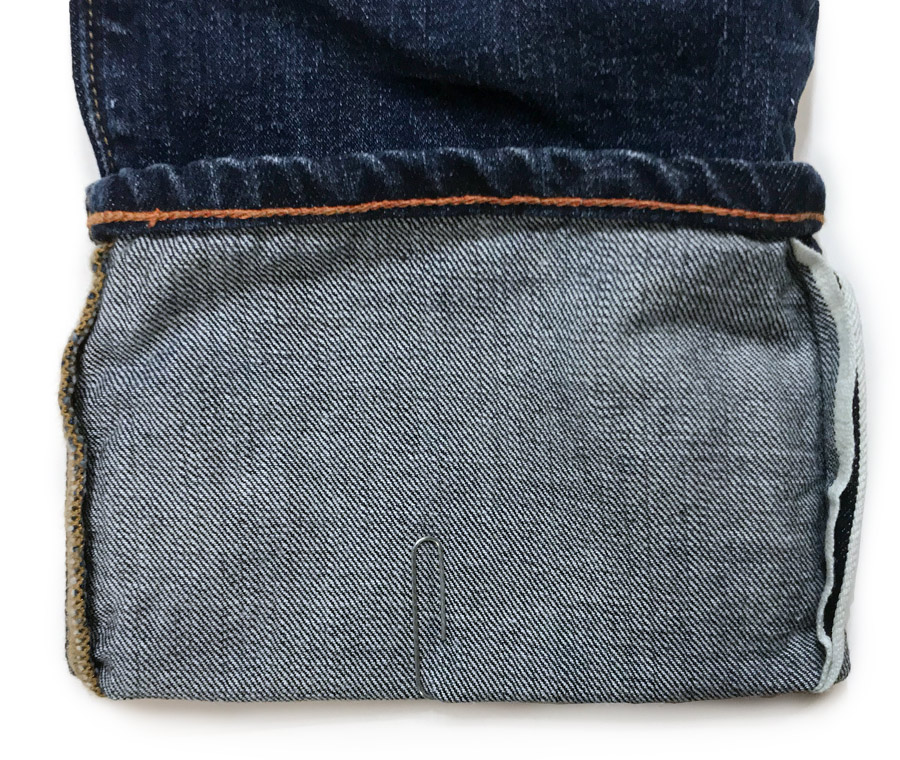 cuffed hem of jeans held in place by a paperclip