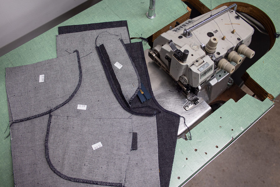 Denim jeans parts sewn with 4-thread overlock sewing displayed on top of the machine