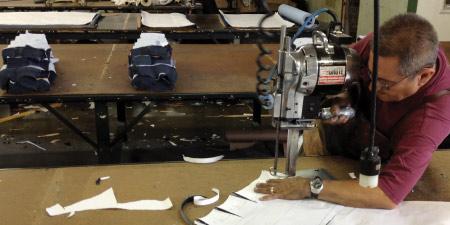 man cutting raw denim american made jeans in manufacturing
