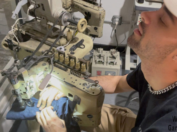 Jeans tapering expert Israel Giles shows off his sewing skills on the Union Special feed off the arm sewing machine.