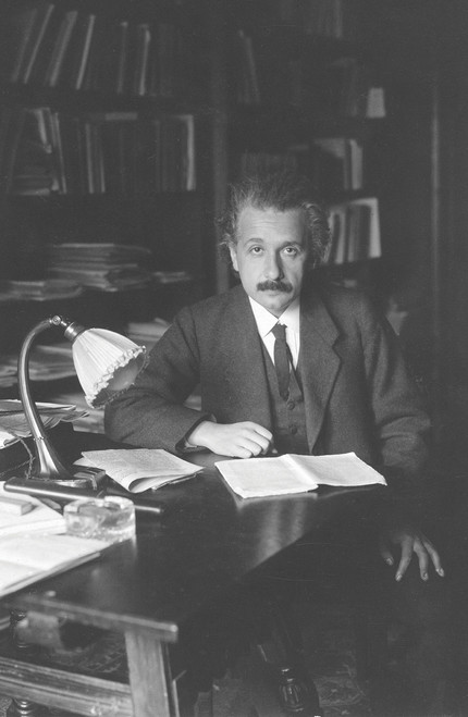 Albert Einstein at his desk with papers and ornate lamp.