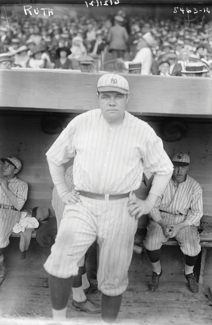 Babe Ruth standing in the dugout at a baseball game.