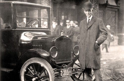 Henry Ford standing in front of the Model T in black and white.