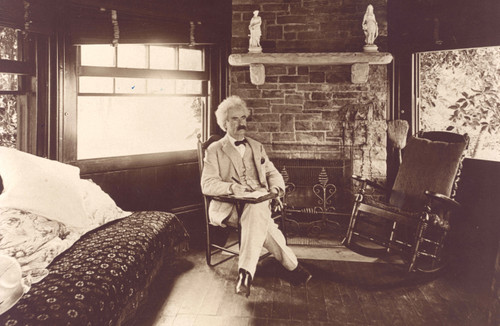 Photo of Mark Twain sitting in his writing cabin in sepia.