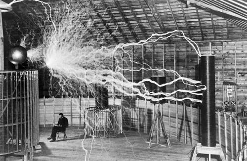 Nikola Tesla writing in his journal in his lab.