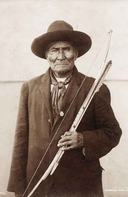 Sepia portrait of Geronimo with bow and arrow.