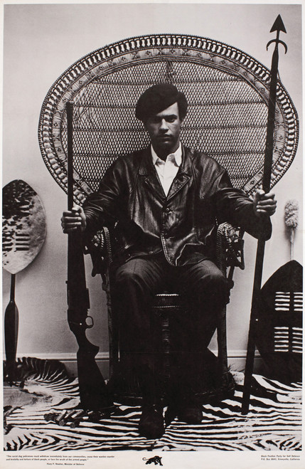 Huey P Newton sitting in peacock rattan chair in black and white.