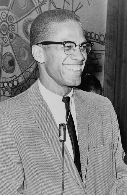 Malcom X smiling in black and white.
