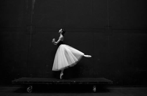 Ballerina in stage lighting holding pose en pointe.