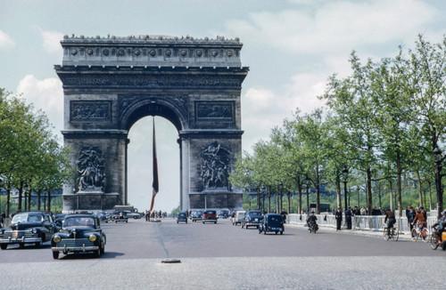Vintage photograph of the Arc de Triomphe in Paris with cars.