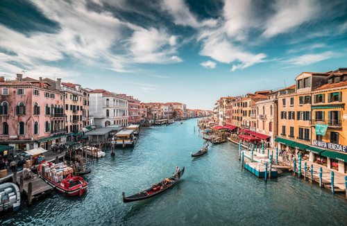 Venice canal with blue sky and gondolas.