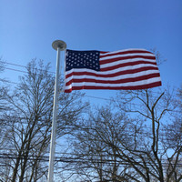 Polyester American Flag flying high and proud on 20' flagpole All 100% Made in the U.S.A.