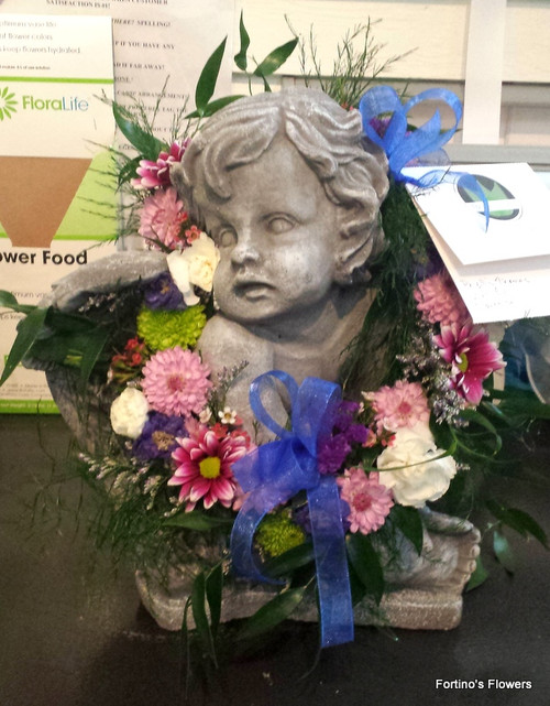 Seated cherub with floral garland